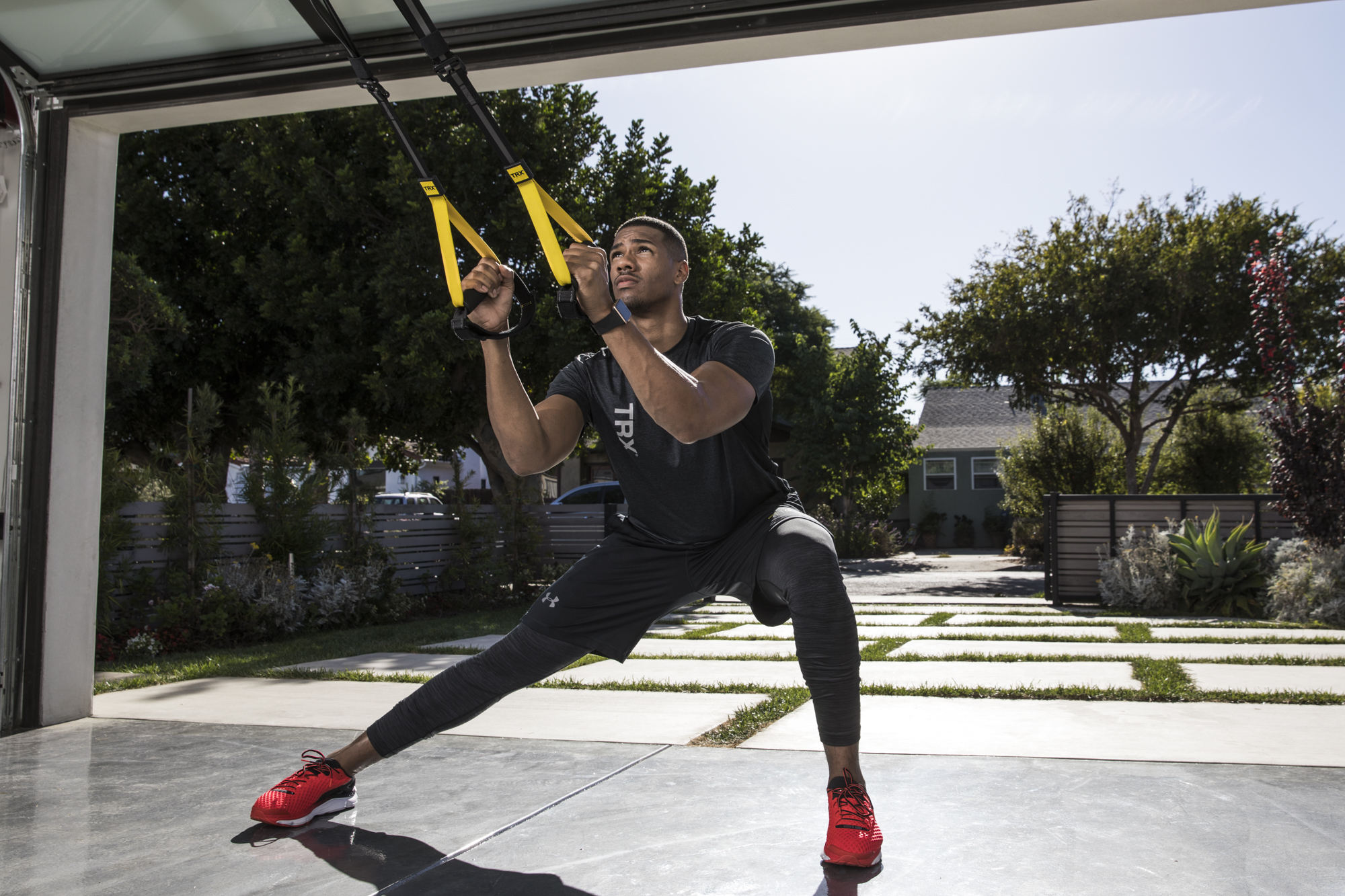 young man performing a side lunge exercise in garage on TRX Suspension Trainer