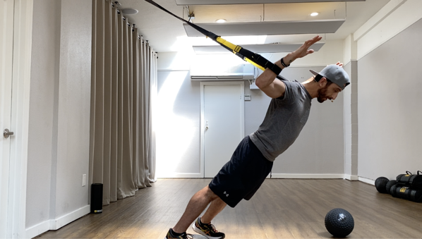 man performing a modified TRX fly at home on TRX Suspension Trainer