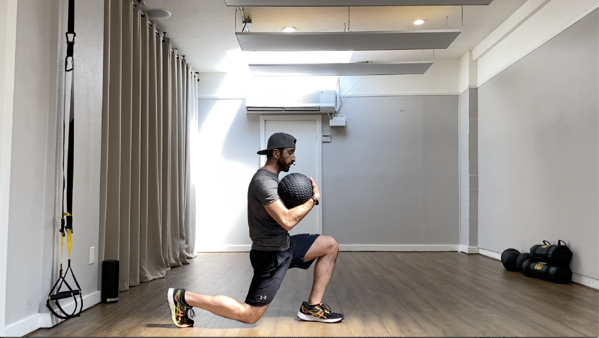 man performing a lunge while holding a slam ball, at home