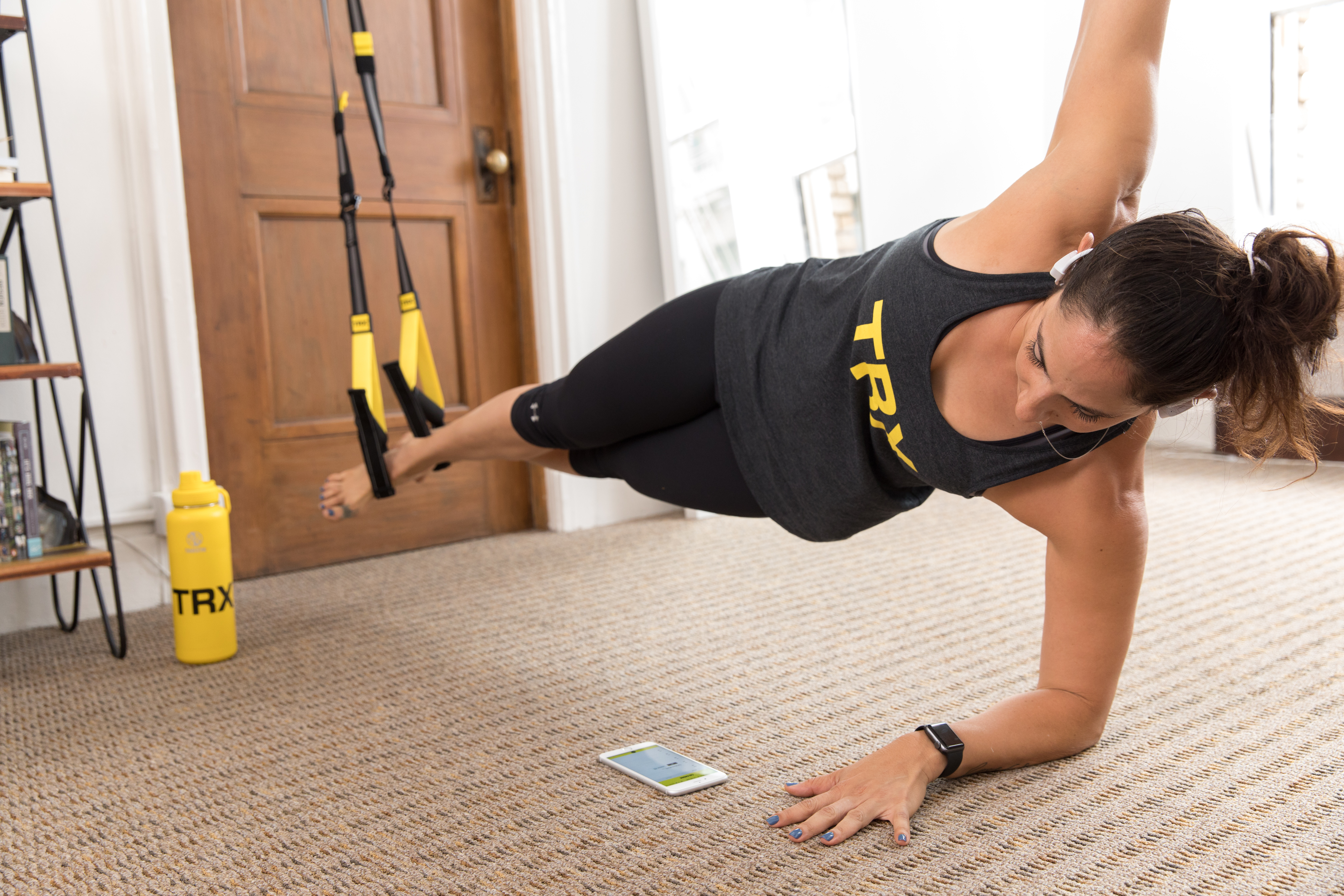 woman performing side plank on TRX Suspension Trainer