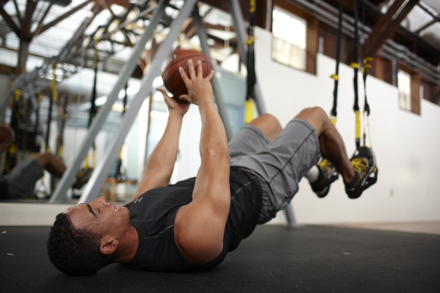 man laying down with basketball in hand while performing a TRX hip press