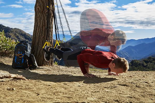man performing a TRX Atomic Pushup outside