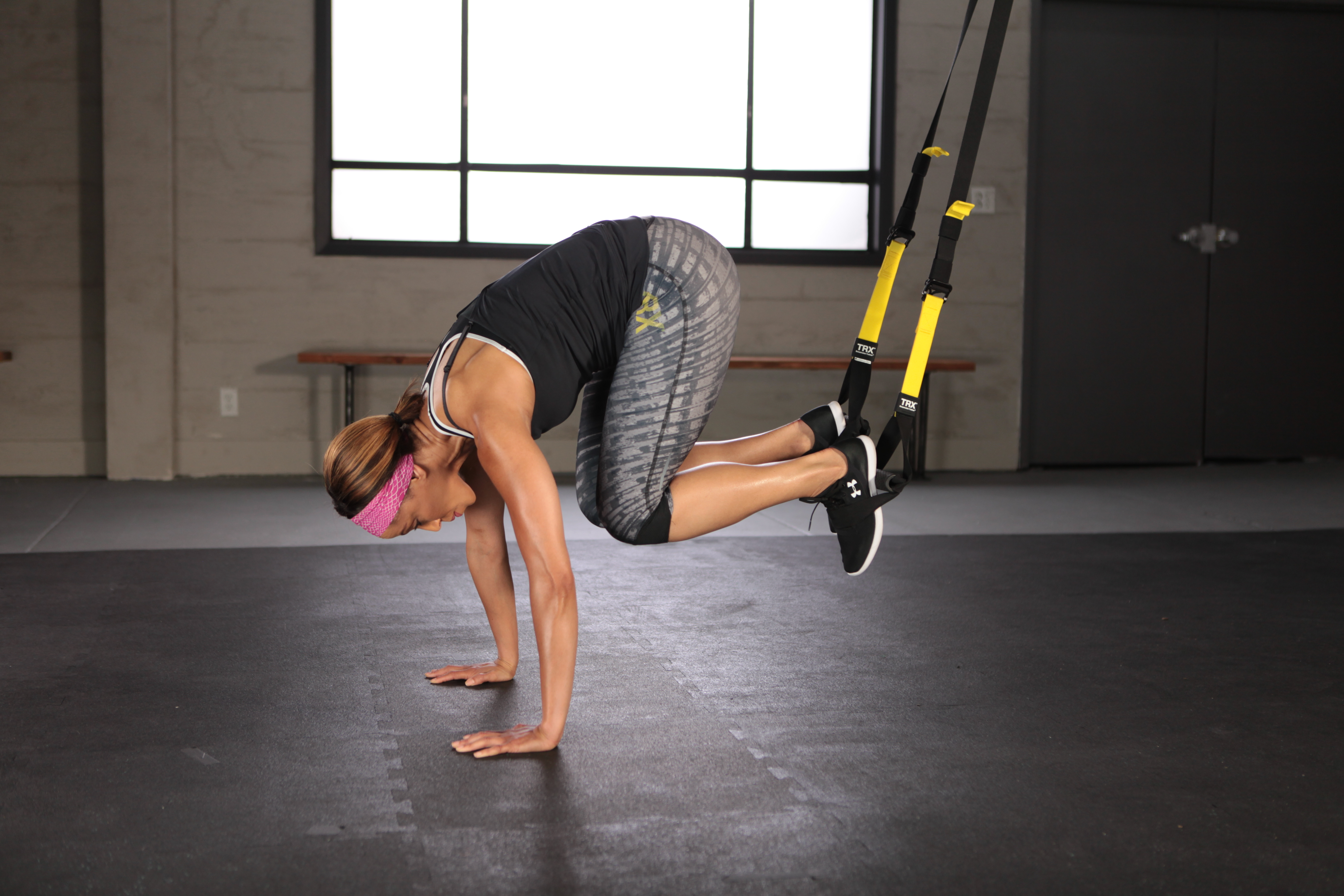 woman performing TRX Atomic Push Up in gym