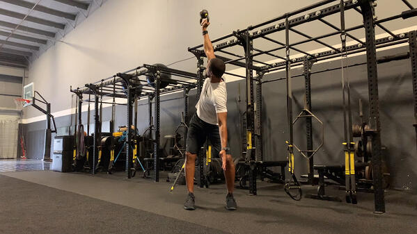 mand doing TRX Kettlebell Rotational Press exercise in gym