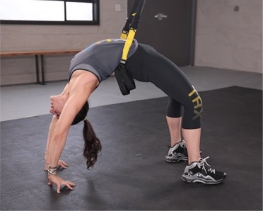woman doing yoga backbend wheel pose on TRX Suspension Trainer