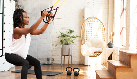woman in a squat using TRX at home