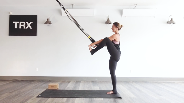 woman on TRX Suspension Trainer Lifting leg to a higher tree pose
