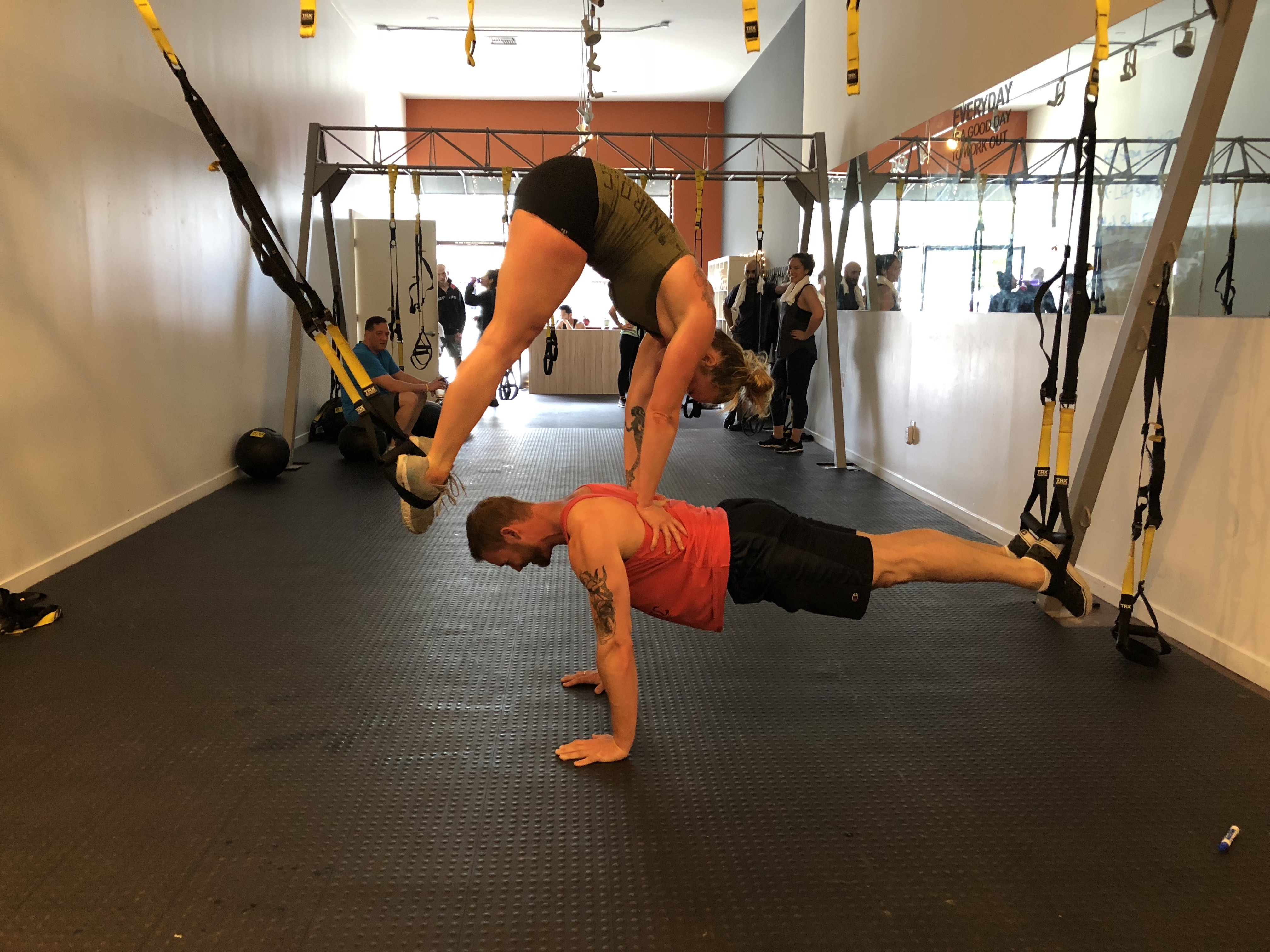 One trainers performing a TRX Atomic Pushup while her hands on a man's back as he performs a TRX Plank