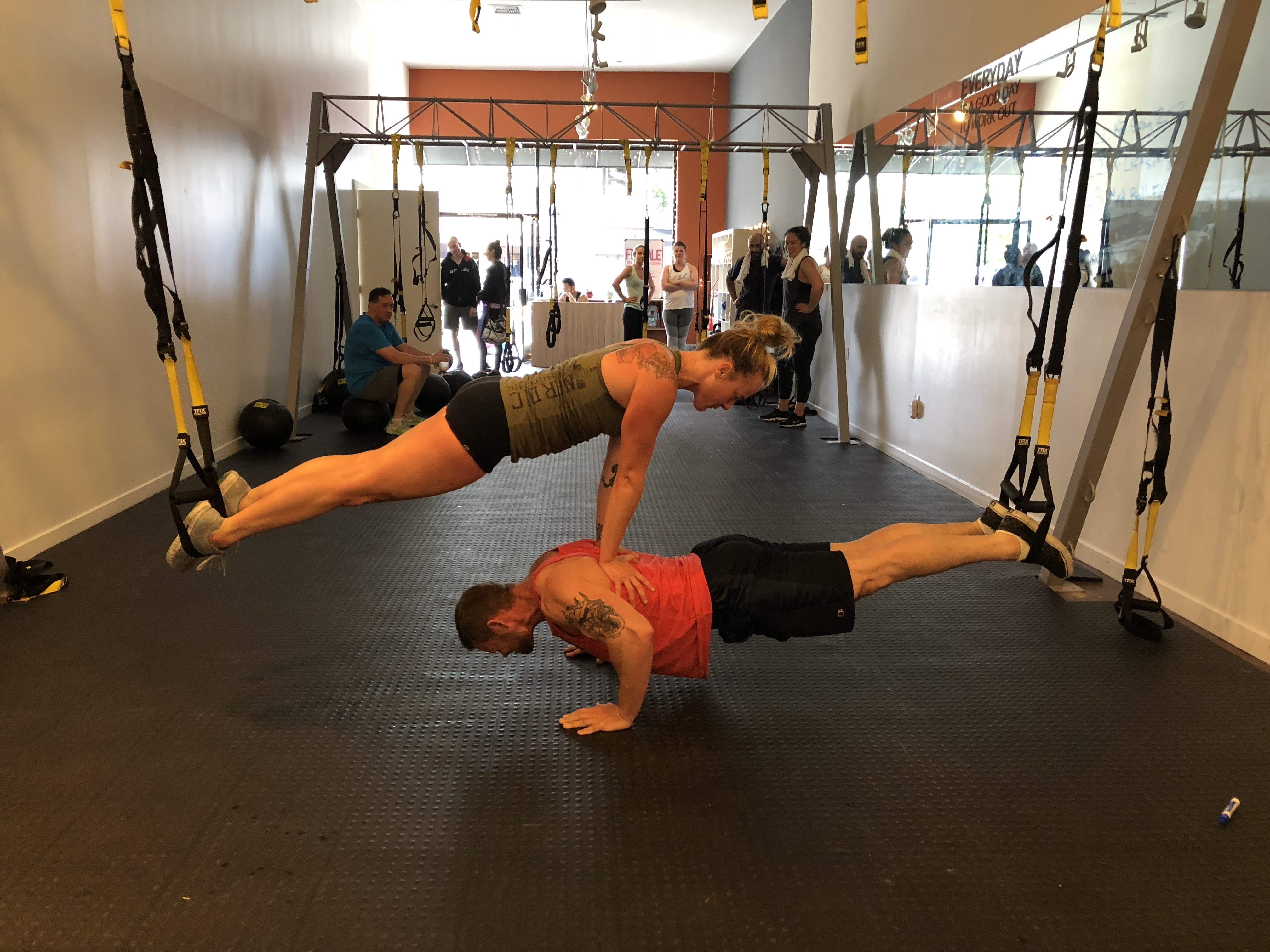 Two trainers perform TRX push ups while stacked above on another