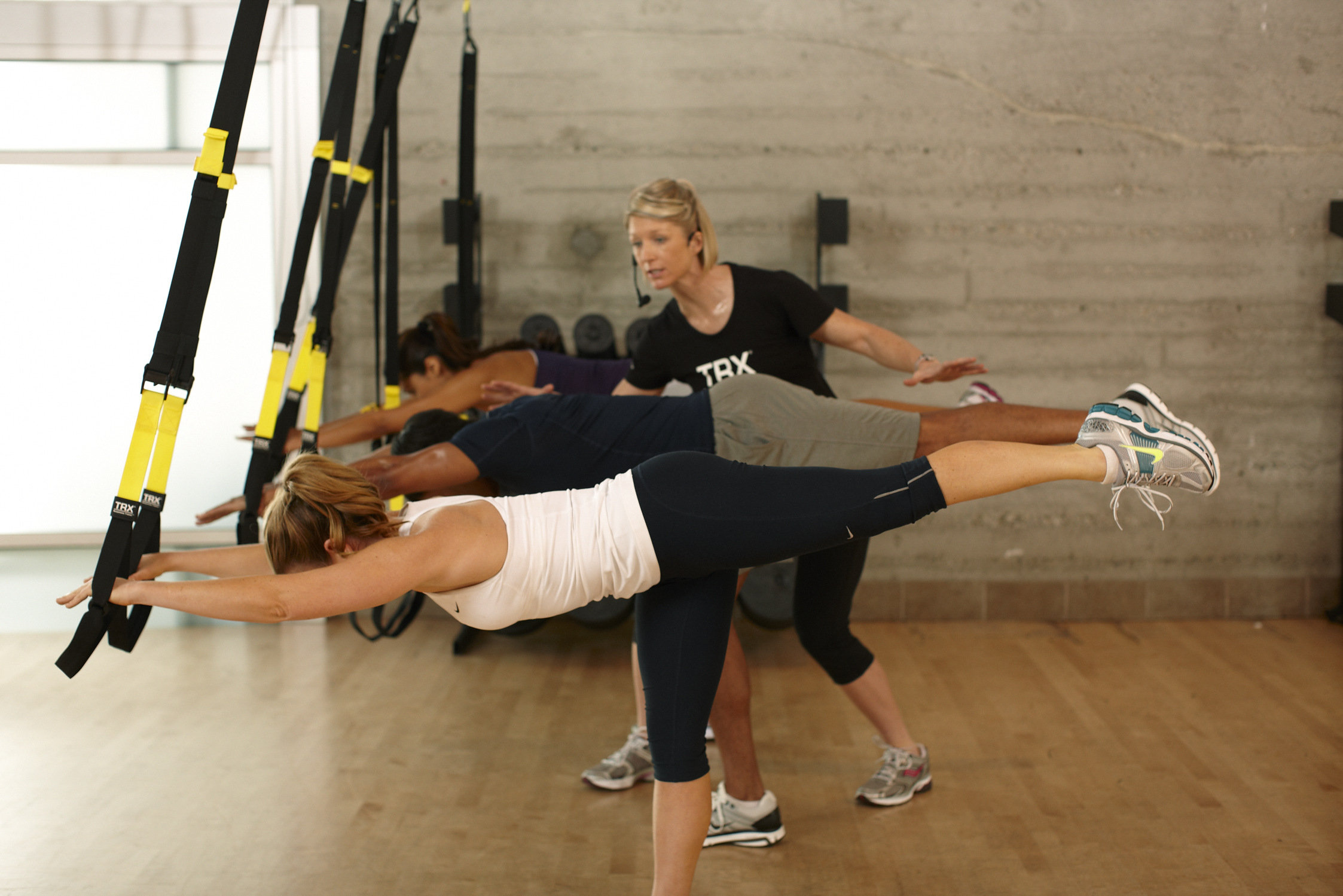 woman teaching group class on TRX Suspension Trainers