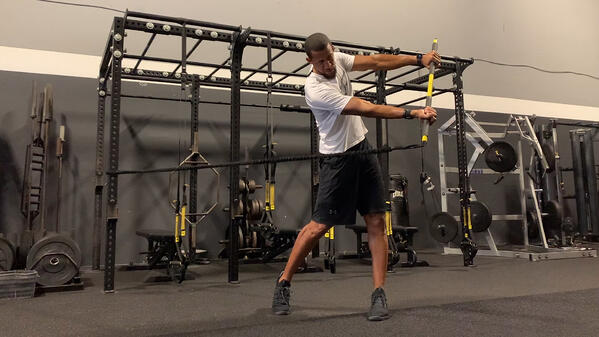 man doing TRX RIP TRAINER Golf Sequence exercise in gym