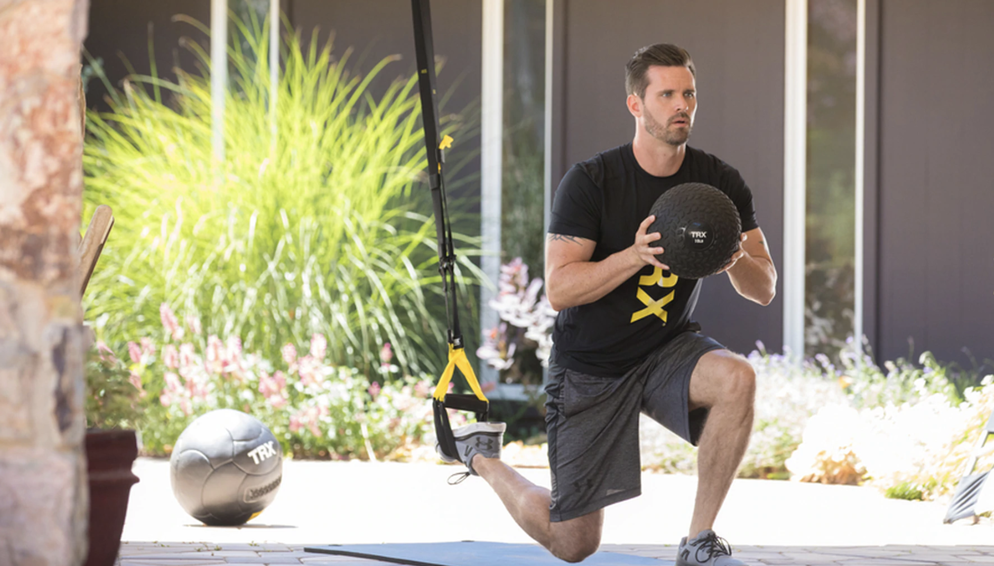 Man in single leg lunge with slam ball