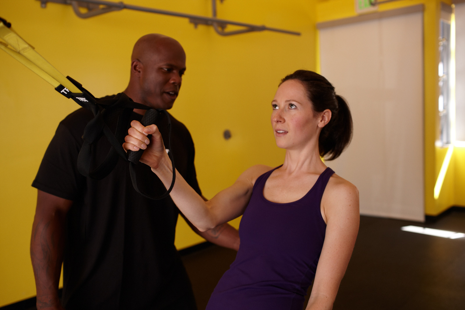 trainer coaching a client in performing a single arm exercise on TRX Suspension Trainer