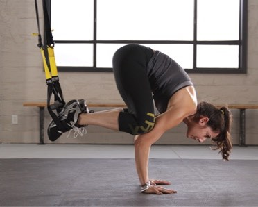 woman doing yoga crow pose on TRX Suspension Trainer