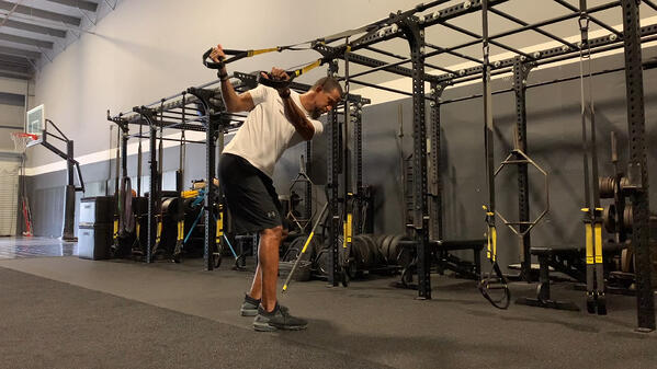 man performing TRX Advanced Golf Rotation in gym