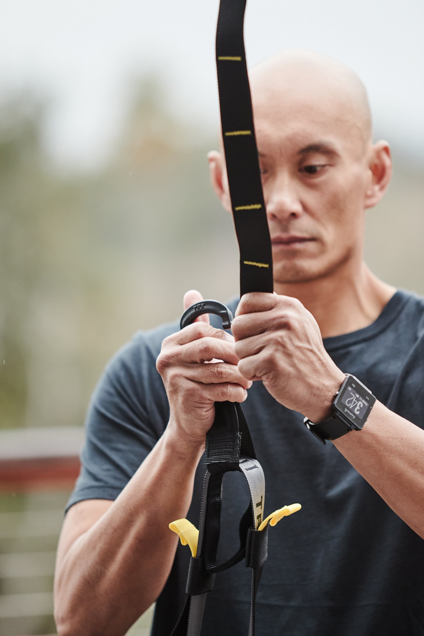 Jamel Ramiro, wearing a black short sleeve t-shirt and a black watch on his left wrist, clips his TRX Suspension Trainer onto its anchor.