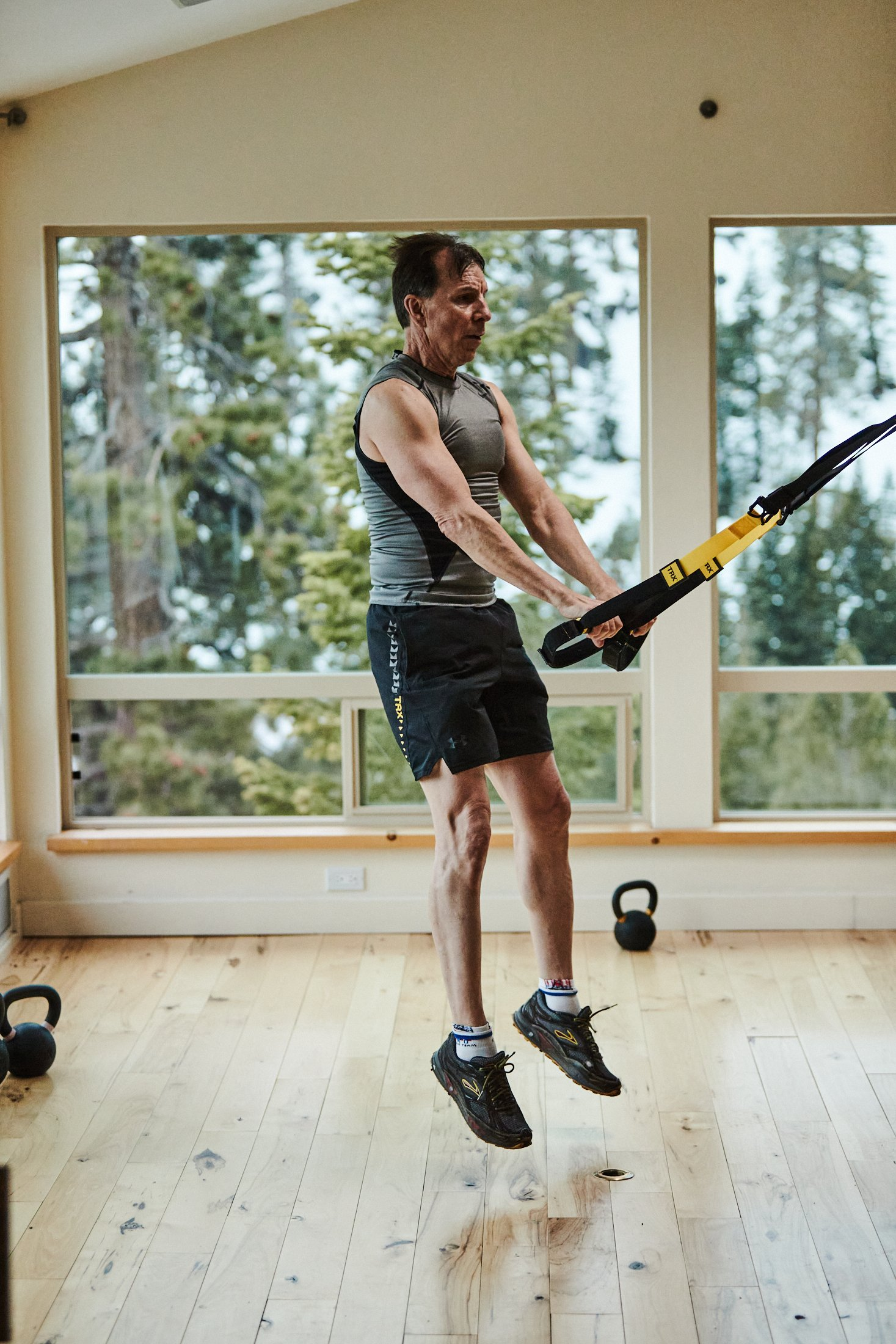 Walt Raineri, wearing a grey sleevess top, black shorts, and black sneakers, does a TRX squat jump. He's in a large room with windows overlooking snowcapped trees.