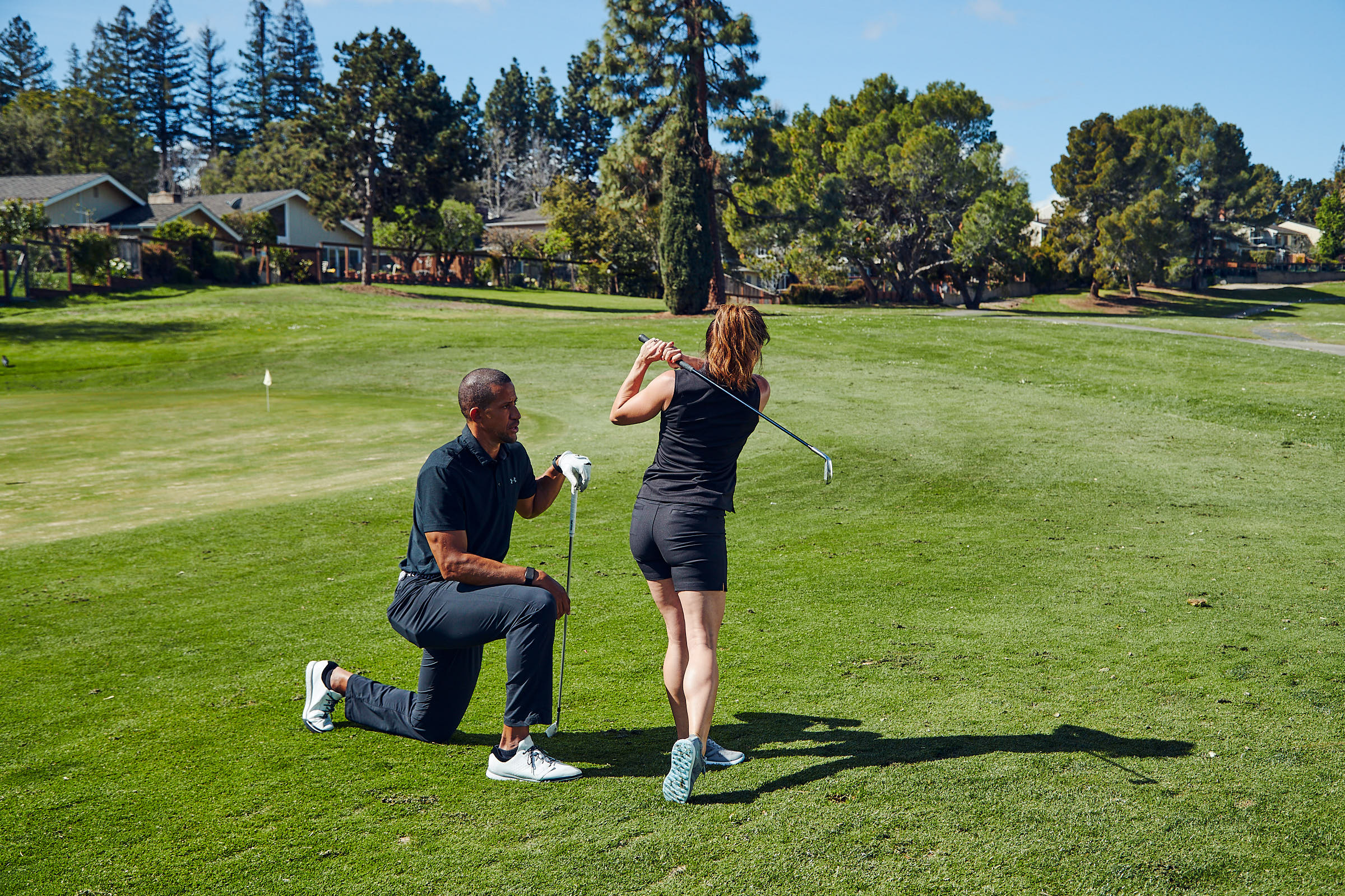 Trevor Anderson coaches female golfer on the golf course