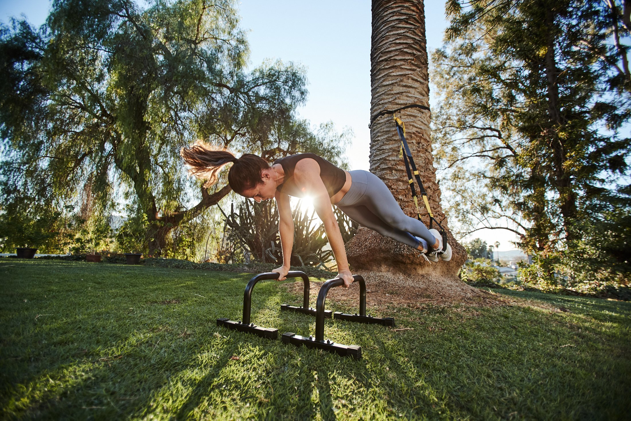 Kristin Leffel, wearing a black top and grey leggings, in a TRX plank outside. Her Suspension Trainer is mounted on a palm tree and her hands are on parallettes