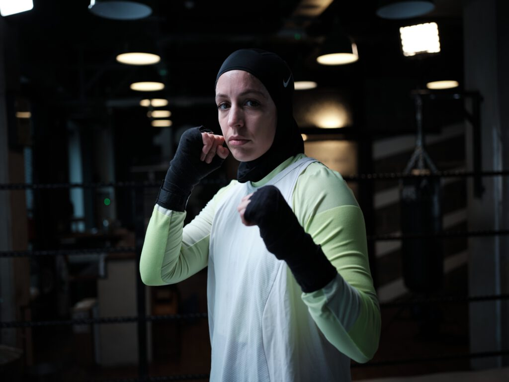Nesrine Dally in a fighting position. She wears a black hijab, black handraps, white vest, and longsleeve green shirt. She is in a boxing gym.