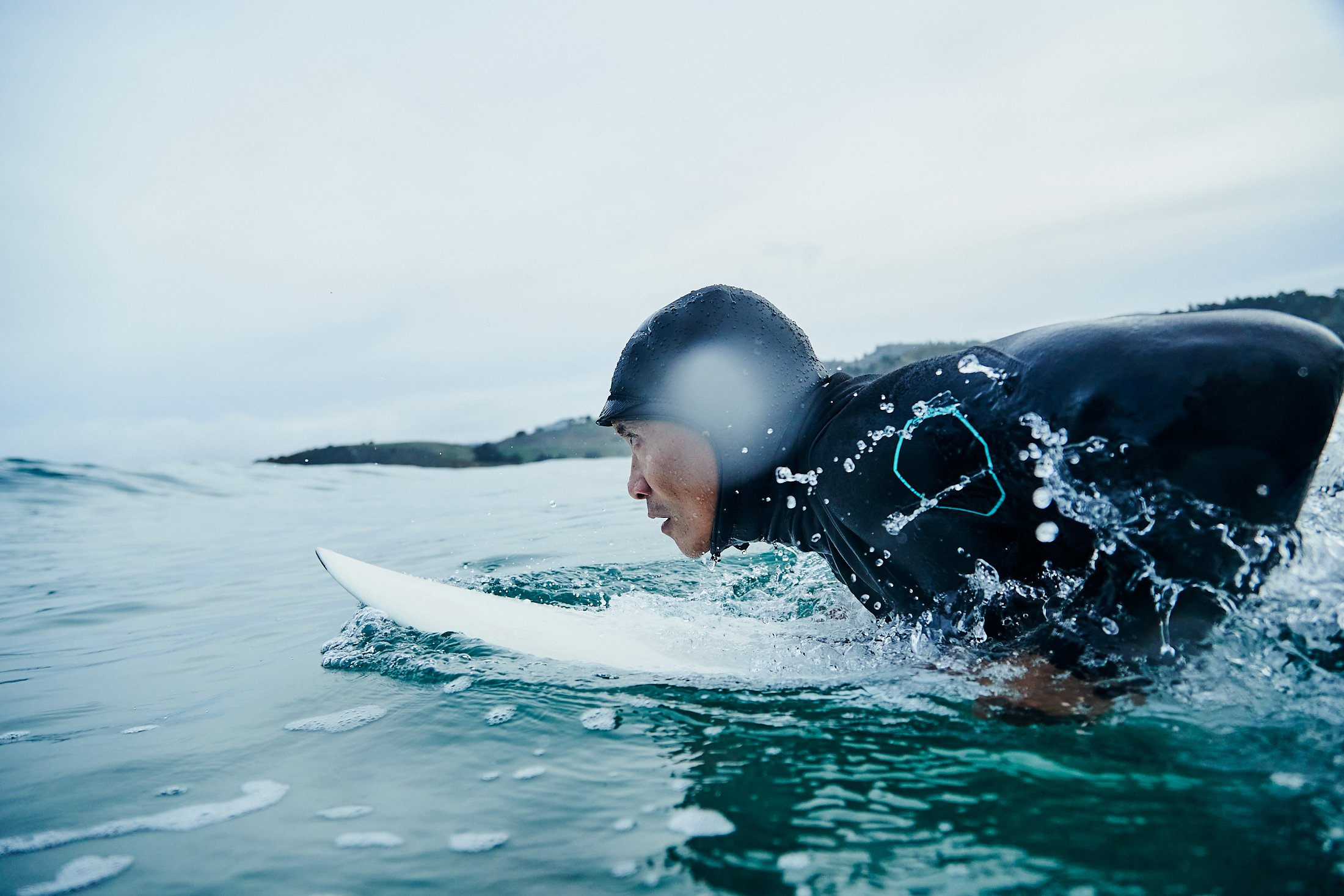 Jamel Ramiro waits for a wave on his surfboard. He is lying on his stomach, watching the horizon. He's wearing a black, full body wetsuit with a head cover. His surfboard is white.