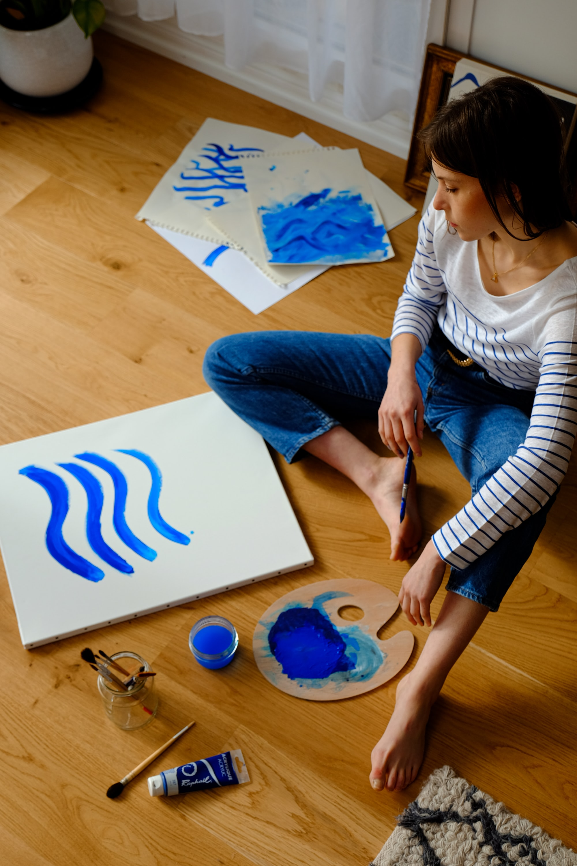 Woman, wearing striped shirt and jeans, sits on the floor and paints a canvas with blue wavy lines. matthieu-jungfer-kBuAJnv31aQ-unsplash