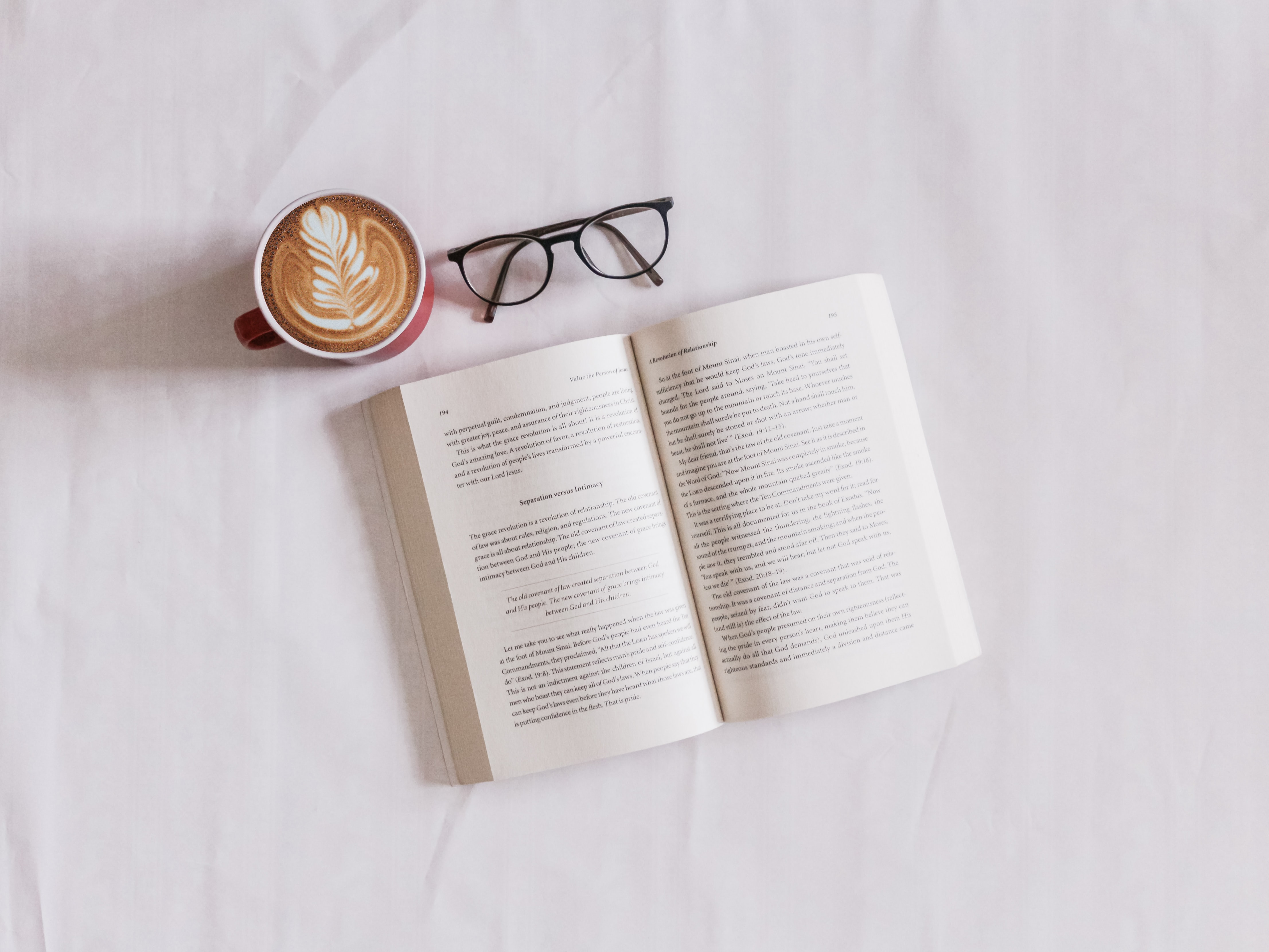 Flat lay photo of a latte with leaf foam art, black eyeglasses, and an open book on a white backgroundsincerely-media-nGrfKmtwv24-unsplash