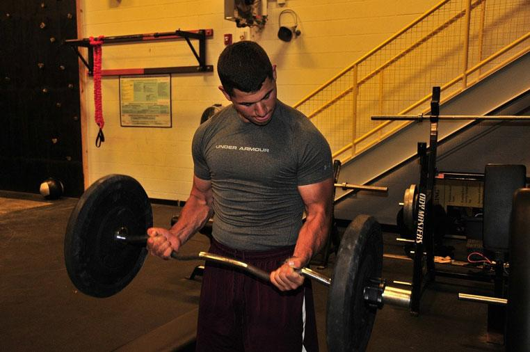 Man Lifts Weights in Gym