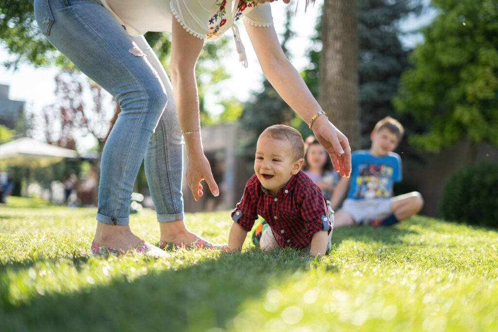 A baby crawls in the grass with two children watching in the background. A woman is reaching down toward the child