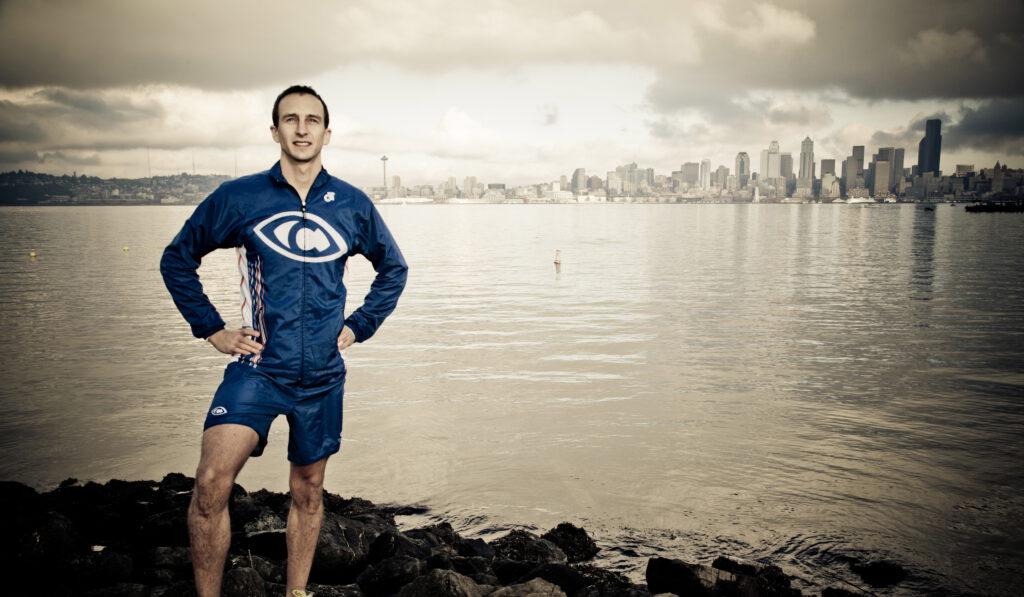 Aaron_Scheidies_in_triathlon_uniform_in_front_of_the_sound_in_seattle